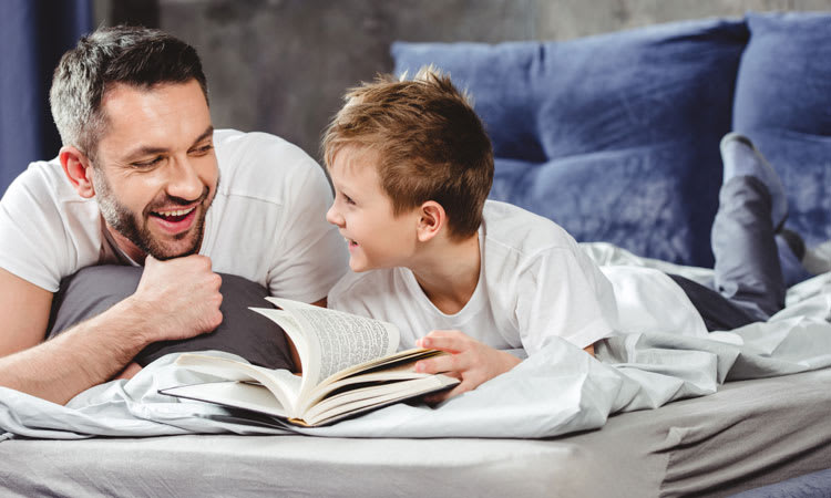 Father and Son Reading a book in Bed