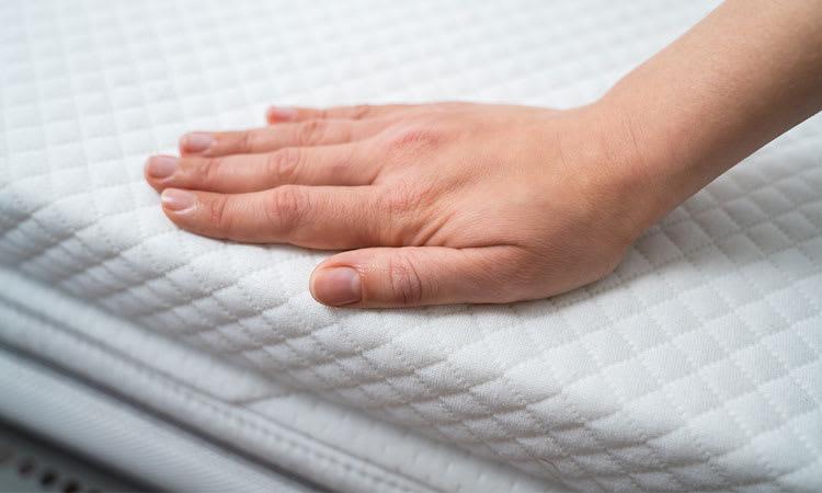 Hand touching the Combination Mattress