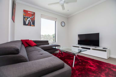 The shaggy, red rug in the lounge room is so soft you might not even use the...