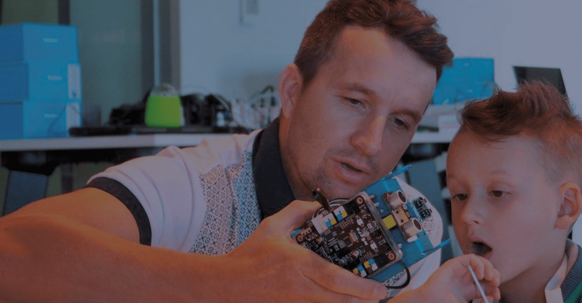 Educator showing robot with circuit board to rapt child