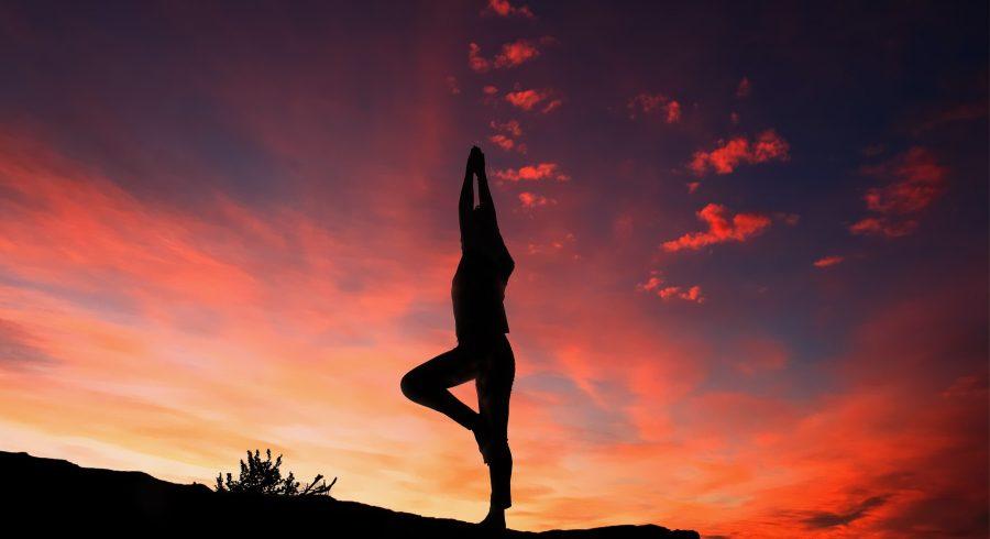 Mit Thai Yoga die innere Mitte finden: Eine Frau macht Yoga Übungen bei Sonnenuntergang