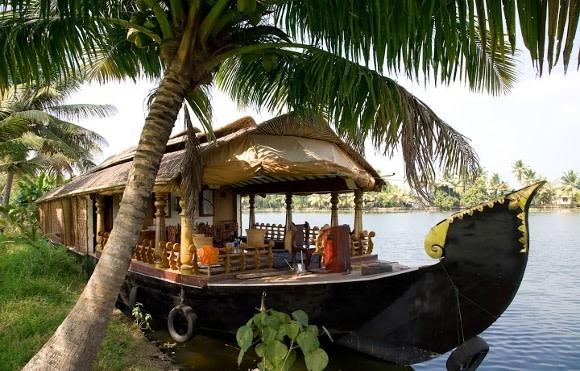 Hausboot mit Strohdach am Flussufer in Kerala, Indien