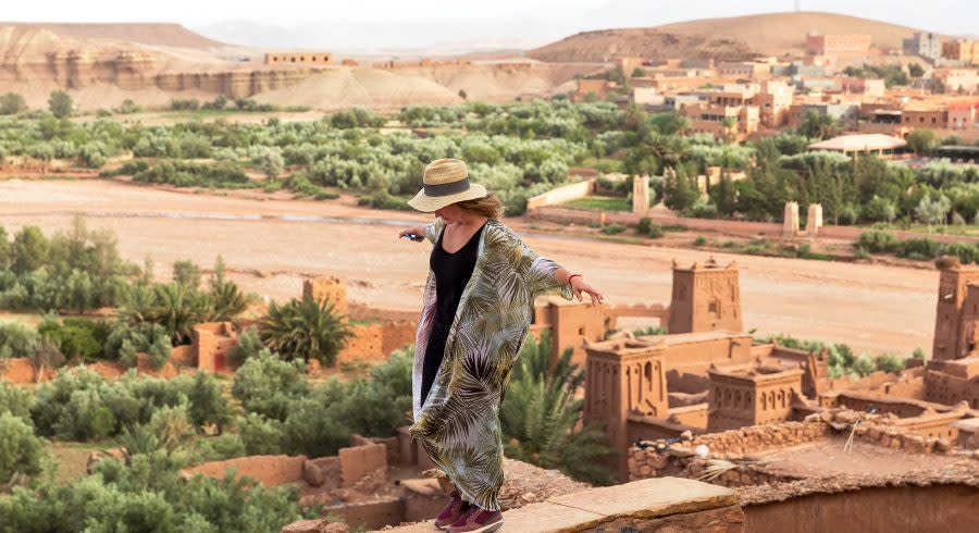 The girl-traveler in a hat is standing on a high wall with arms outstretched in the background of the city in the desert of Ait BenHaddou, Morocco, Africa