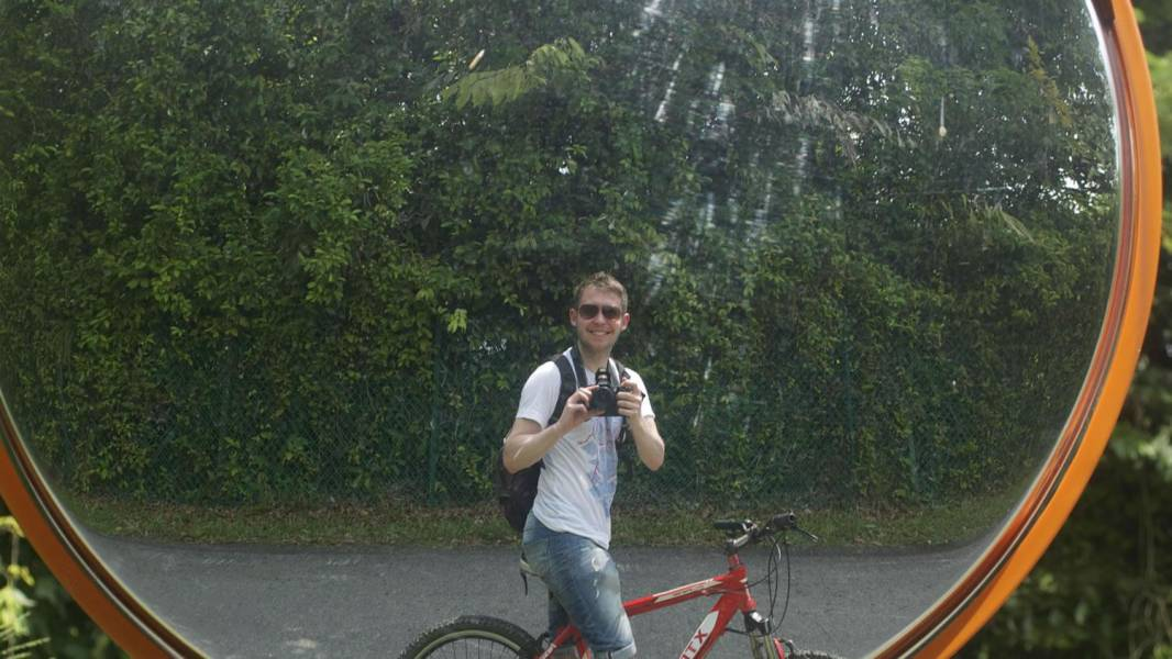 a man riding a bicycle in front of a mirror posing for the camera