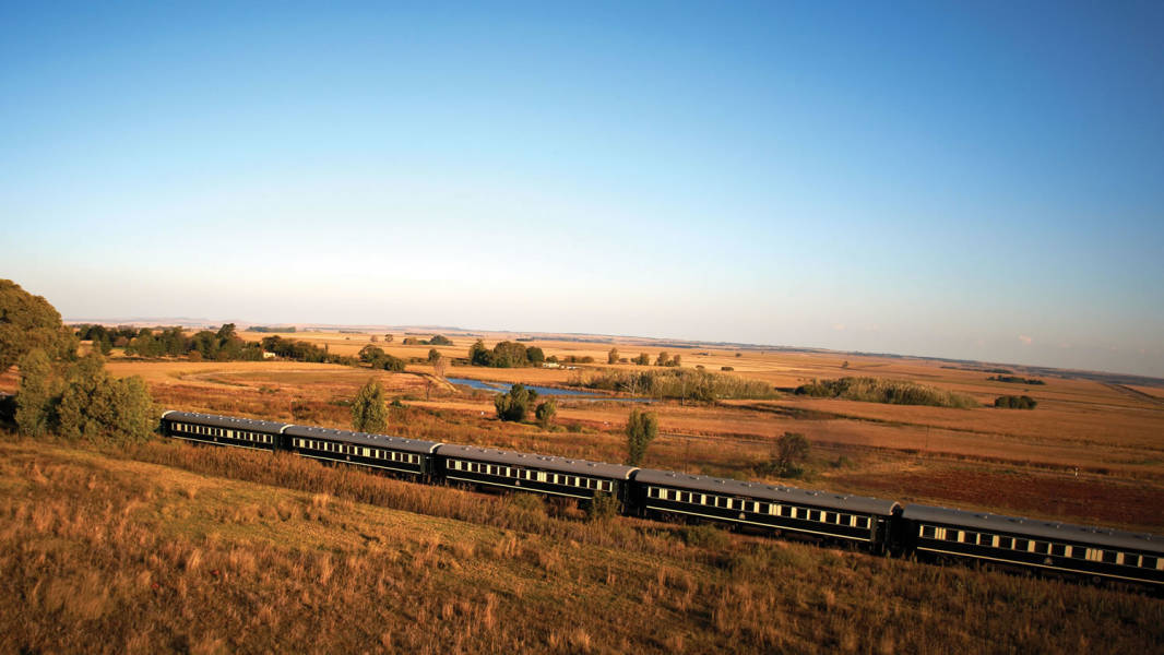 a large long train on a track near a field