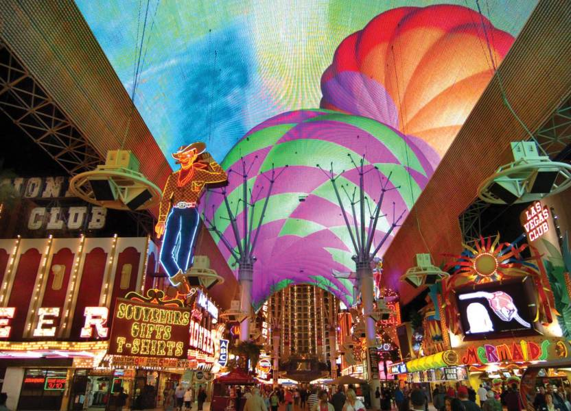a group of colorful buildings with Fremont Street Experience in the background