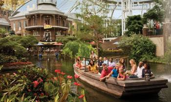 a group of people on a boat in the water with Gaylord Opryland Resort & Convention Center in the background