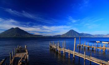 a wooden pier next to a body of water with Lake Atitlán in the background