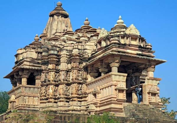 a large stone building with a clock tower with Khajuraho Group of Monuments in the background