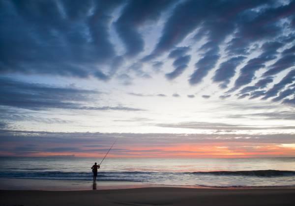 a man flying a kite on the beach
