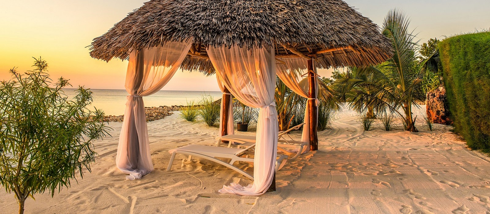 Beach lounge chairs at sunset at the shore of Indian ocean, Zanzibar, Tanzania, Africa Enchanting Travels
