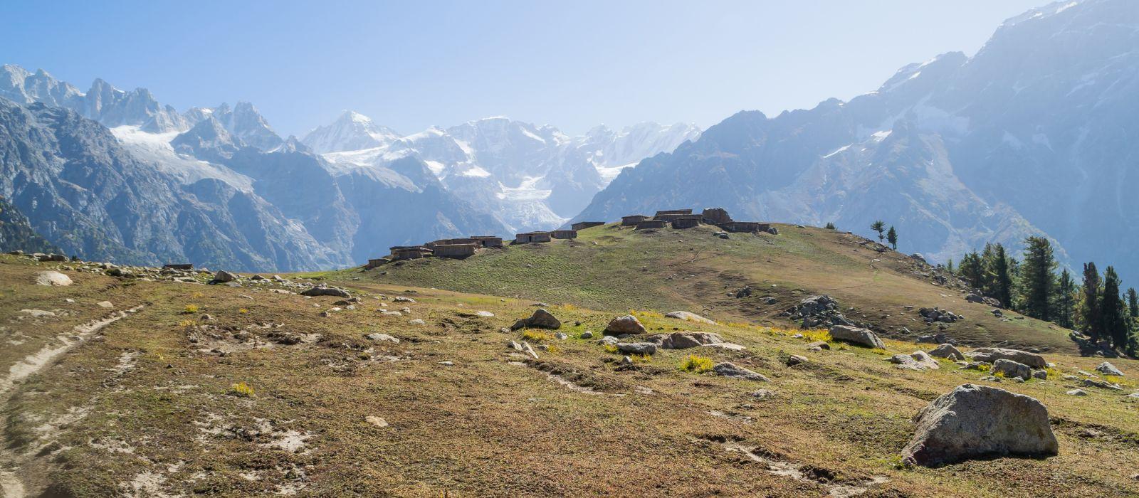 Lokale Siedlungen auf einer riesigen Wiese im Herbst mit Gletschern und hohen Bergen im Hintergrund, Nepal, Asien