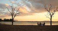 Menschen bei Sonnenuntergang am Strand