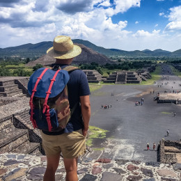 A Mexican American tourist with a backpack and hat