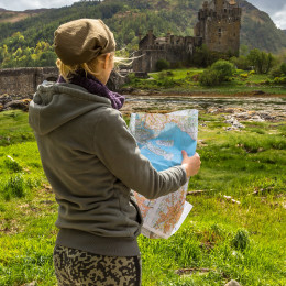 Young woman tourist looks at a road map. In background the famous and spectacular Eilean Donan Castle in Dornie, Kyle of Lochalsh, Scotland, United Kingdom