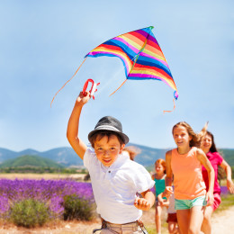 Happy boy flying rainbow kite with his friends