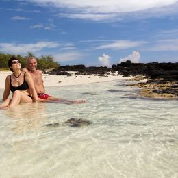Enchanting Travels Mauritius tours couple is sitting together on a white sand beach