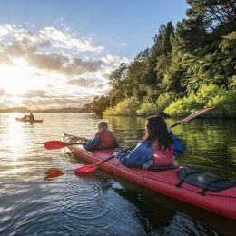 Zwei Kanuten auf dem Fluss Rotoiti in Rotorua, Neuseeland fahren in den Sonnenuntergang