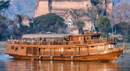 Traditionelles Boot aus Teakholz vor felsiger Uferlandschaft