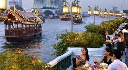 Elegant gekleidete Menschen dinieren am Flussufer in Bangkok
