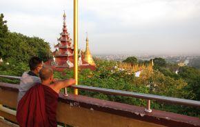 Ein junger Mönch und ein Junge genießen die Aussicht vom Mandalay Berg auf die Stadt und die goldene Pagode im Hintergrund