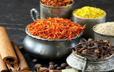 Schalen mit typisch indischen Gewürzen (Paprika, Kurkuma, Pfeffer, Anis, Zimt, Safran)