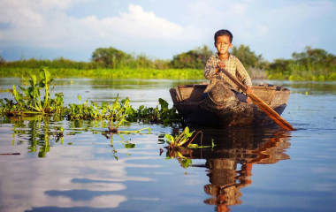 Junge in Kambodscha rudert im Kanu