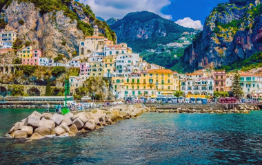 Enchanting Travels Italy Tours Wonderful Italy. The small haven of Amalfi village with a turquoise sea and colorful houses on the slopes of the coast