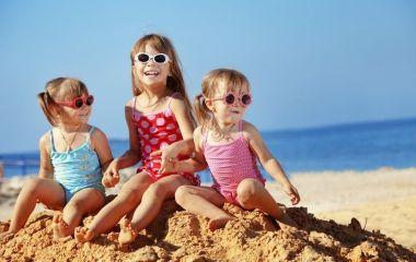 Drei kleine Mädchen mit Sonnenbrillen lachen am Sandstrand