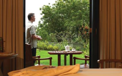 Mann steht am Gartentisch einer Lodge und trinkt Tee