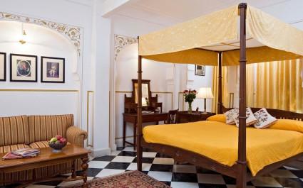 Schlafzimmer mit Himmelbett und antiken Holzmöbeln im Hotel Samode Haveli, Indien