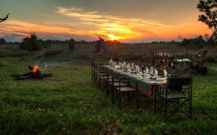 Gedeckte Tische im Freien bei Sonnenuntergang im  Kanana Camp, Okavangodelta, Botswana