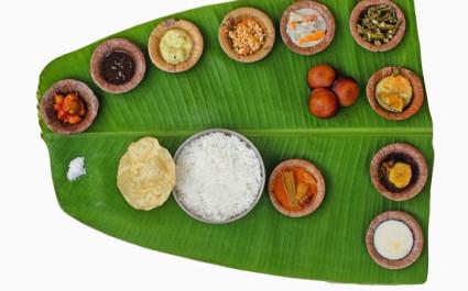 Verschiedene indische Speisen und Reis auf einem großen grünen Blatt