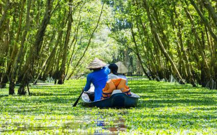 Frau fährt mit Kanu durch den überschwemmten Wald von An Giang im Mekong-Delta, Vietnam