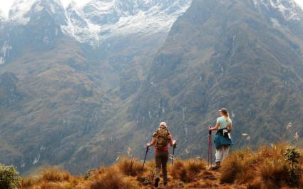 Zwei Wanderer blicken auf Bergkulisse mit schneebedeckten Gipfeln