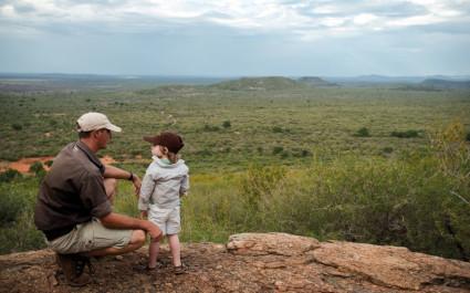 Vater kniet mit seinem kleinen Sohn in der südafrikanischen Wildnis