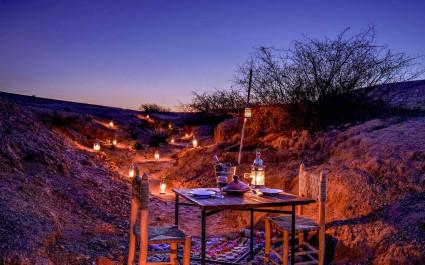 Gedeckter Tisch im Freien für ein romantisches Dinner zu zweit im Agafay Camp