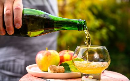 Enchanting Travels France Tours Pouring of french apple cider in glass made from new harvest apples outdoor in sunny orchard - cuisine in France