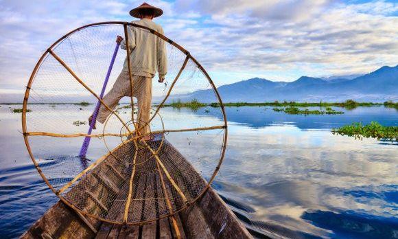 Ein Beinruderer fährt zum Fischen im Kanu auf dem Inle-See in Myanmar