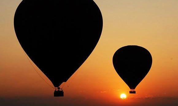 Schatten von Bagan Ballons, während im Hintergrund die Sonne aufgeht