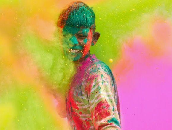 Holi, Fest der Lichter - Junge wird mit Farben beworfen