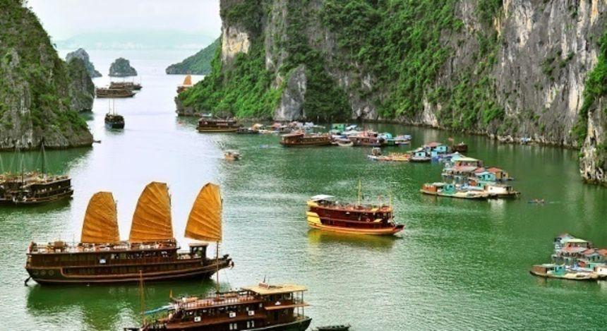 Mehrere Dschunken, Boote und Kreuzfahrtschiffe in der felsigen Halong-Bucht von Vietnam