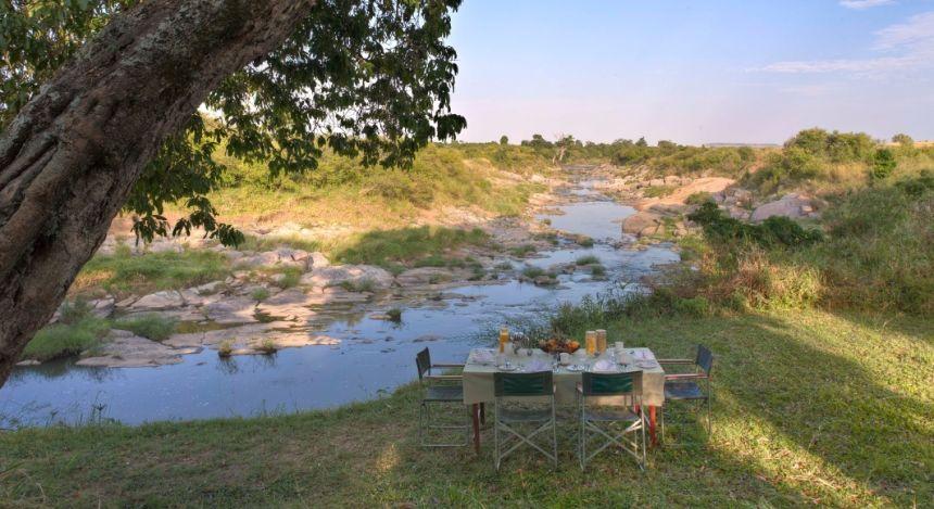 Gedeckter Tisch beim Fluss im Rekero Tented Camp Hotel in Masai Mara, Kenia