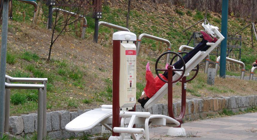 Frau in Fitnessgerät in einem Park in Seoul, Südkorea