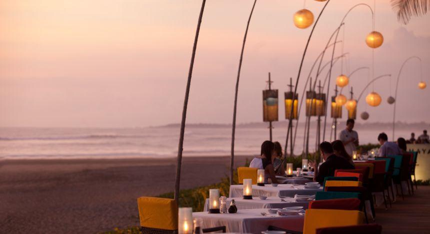 Gedeckte Tische am Strand bei Sonnenuntergang im Samaya Seminyak Bali