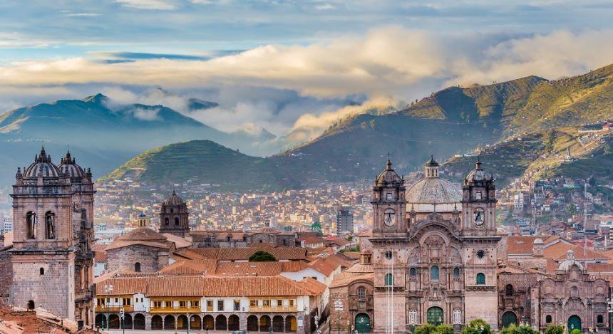 Stadtpanorama von Cusco mit der Kathedrale im Vordergrund und dem bewölkten Anden-Gebirge im Hintergrund, Peru