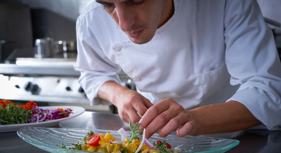 Chef garnishing ceviche dish with hands in stainless steel kitchen