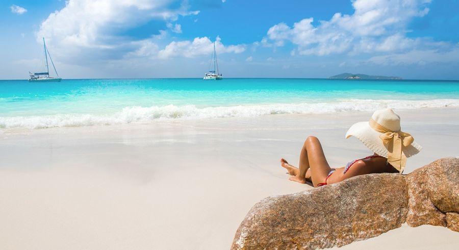 Frau am Strand von Praslin Island - eines der beliebtesten Seychellen Reiseziele