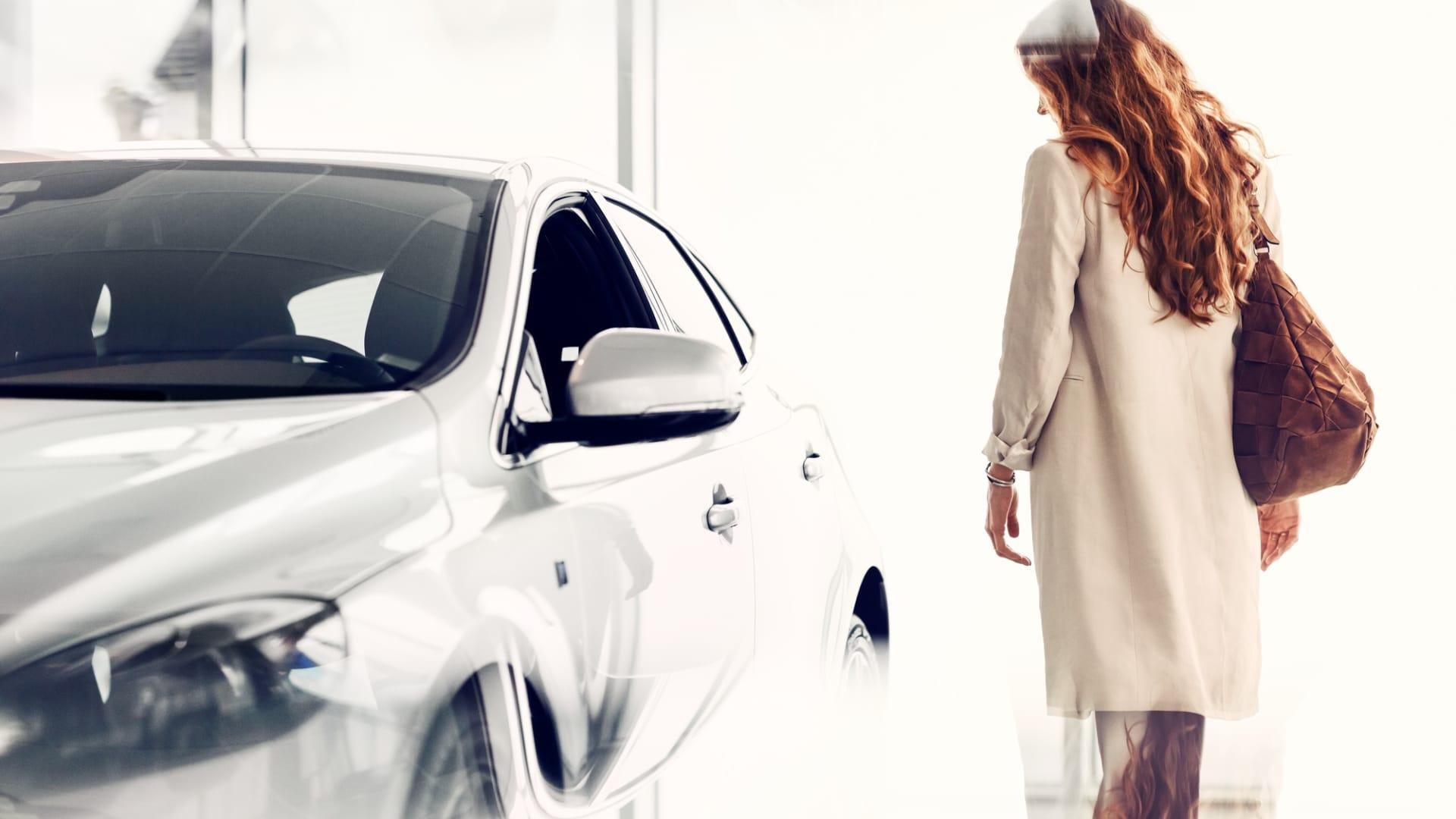 Kvinne ser på hvit bil