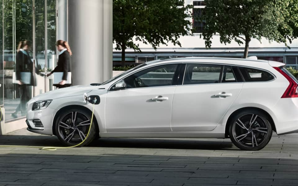 Hvit Volvo V60 Twin Engine Plug-in Hybrid lades med gul ledning i byen foran dame som tar ut penger fra minibanken